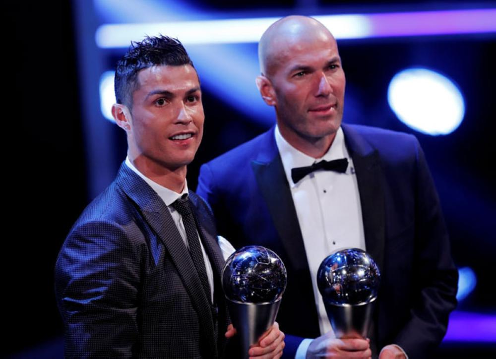 Real Madrid's Cristiano Ronaldo celebrates after winning The Best FIFA Men's Player Award with Real Madrid coach Zinedine Zidane. — Reuters