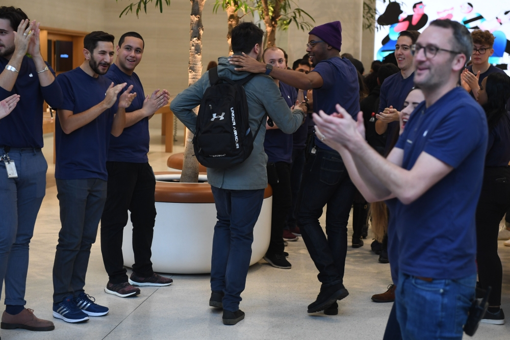 Apple staff congratulate customers as they are of the first to enter Apple's Regent Street store in central London on Friday after it opened for the first sales of the Apple iPhone X smartphone. — AFP