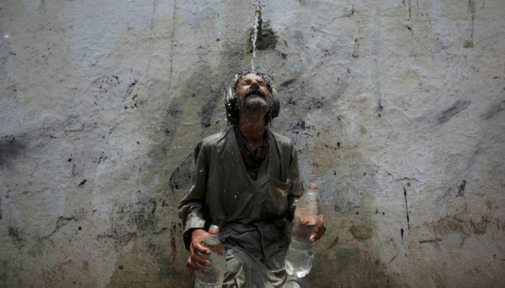 A man cools off from a public tap after filling bottles during intense hot weather in Karachi. — Reuters photos