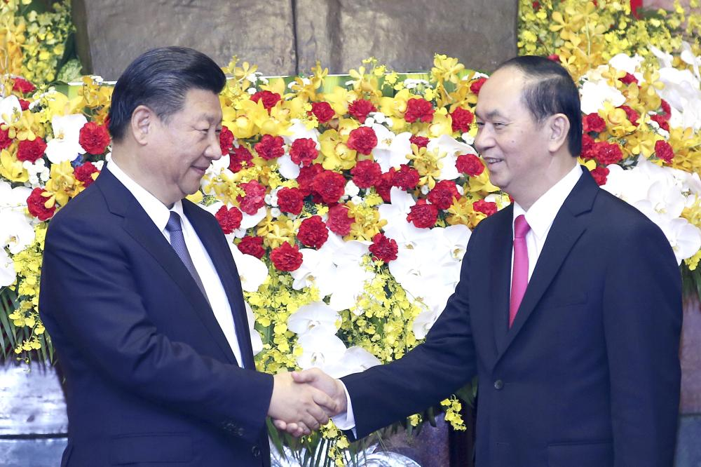 Chinese President Xi Jinping, left, shakes hands with Vietnamese President Tran Dai Quang at Presidential Palace in Hanoi, Vietnam, on Monday. — AP
