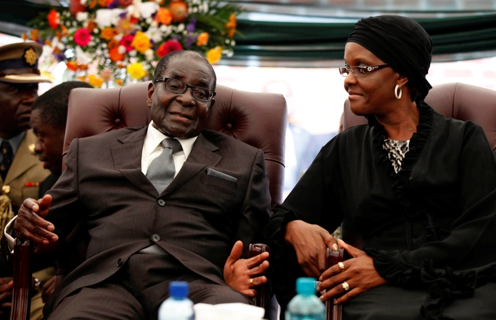 Zimbabwe President Robert Mugabe speaks to his wife Grace during the funeral of his sister, Bridget in the village of Zvimba, in this file photo.  — Reuters