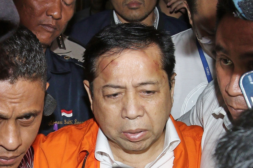 Indonesia's Parliament Speaker Setya Novanto (in orange) is being escorted by officials from the Corruption Eradication Commission (KPK) in Jakarta on Sunday.  — AFP