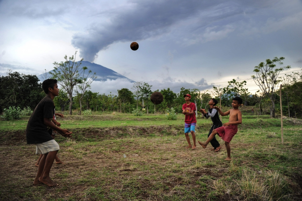 Children play with a ball before Mount Agung in Karangasem on Indonesia's resort island of Bali, Thursday.  Thousands of foreign tourists were expected to leave Bali by plane following a nearly three-day airport shutdown sparked by a rumbling volcano on the Indonesian holiday island. — AFP