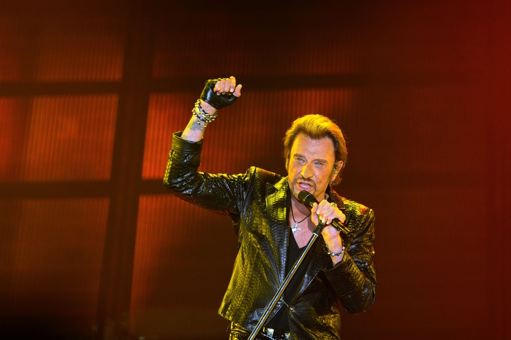 This June 2, 2013 file photo shows French singer Johnny Hallyday gesturing as he performs on stage in Bordeaux, southwestern France. - AFP