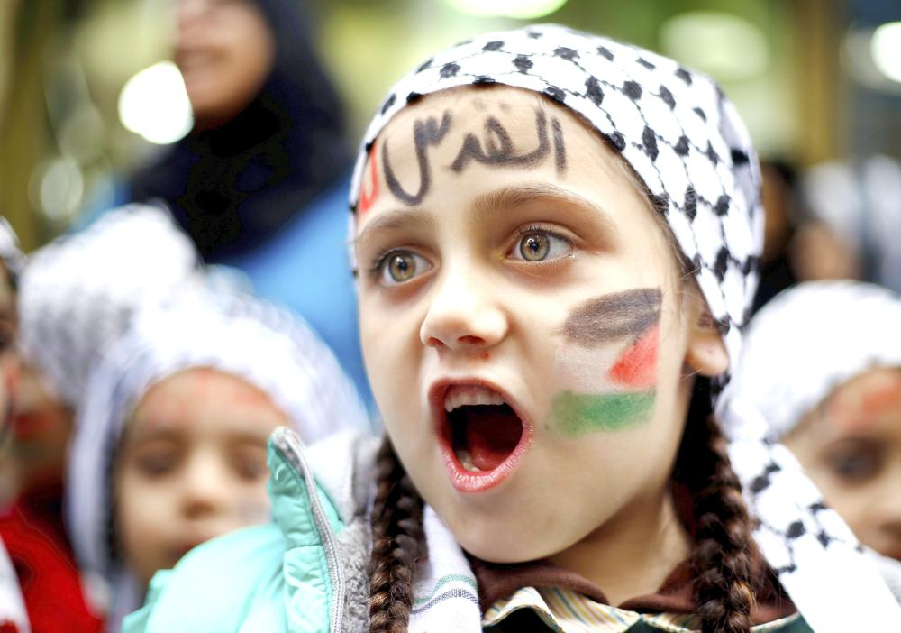 """A girl with a Palestinian flag and Arabic that read """"Jerusalem is for us"""" painted on her face chants slogans during a sit-in in the Bourj Al-Barajneh Palestinian refugee camp in Beirut, Lebanon, Wednesday. — AP"""