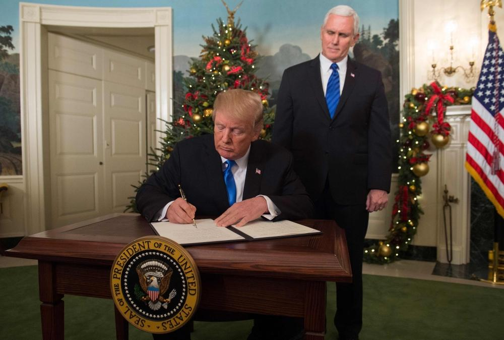 US President Donald Trump signs a memorandum after he delivered a statement on Jerusalem from the Diplomatic Reception Room of the White House in Washington, DC on Wednesday as US Vice President Mike Pence looks on. — AFP