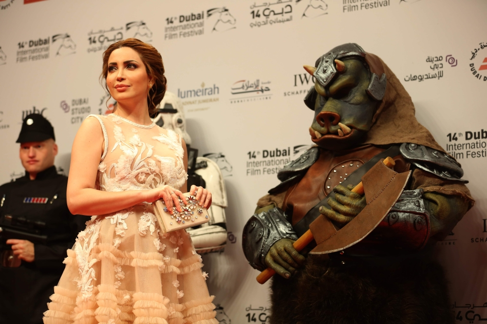 Syrian actress Nesrine Tafesh poses with a Star Wars character as she arrives on the red carpet during the closing ceremony of the Dubai International Film Festival, in Dubai on Wednesday. — AFP