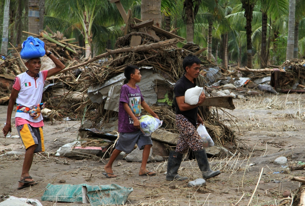 Residents carry relief goods past debris in a village devastated by flash floods in Salvador, Lanao del Norte in southern Philippines, on Sunday. — Reuters