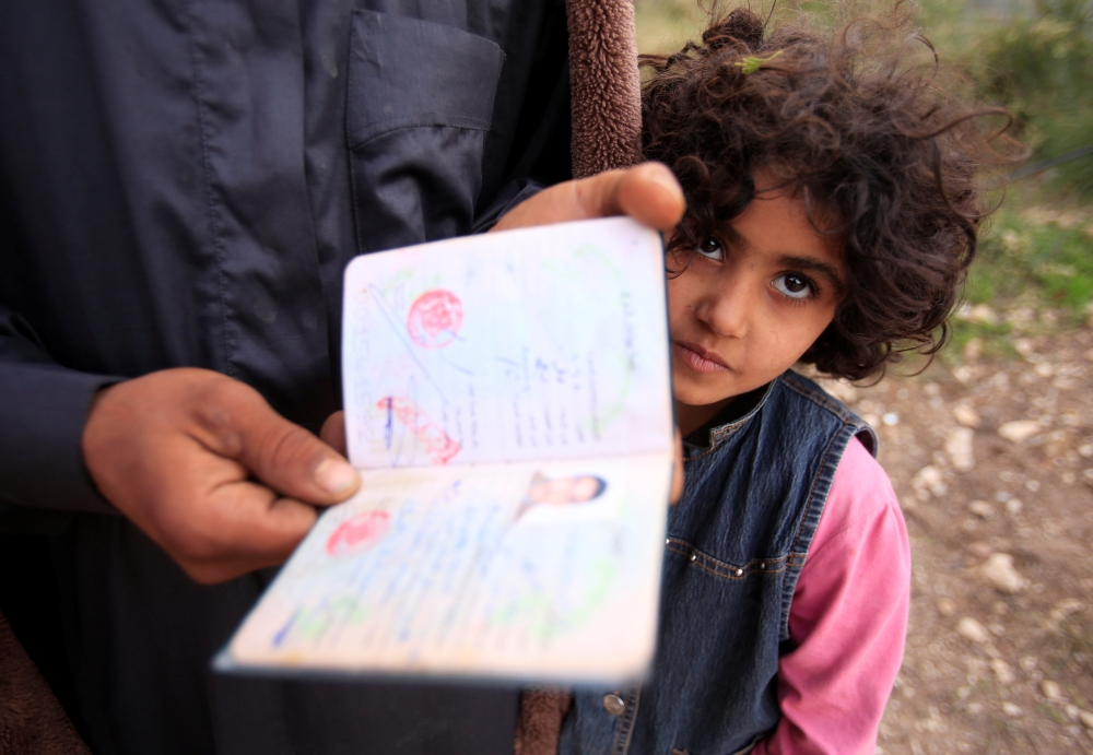 A Syrian refugee man holds a document in Ain Baal village, near Tyre in southern Lebanon. — Reuters