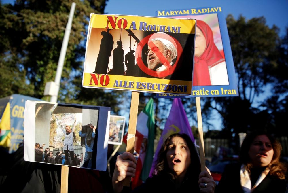 Opponents of Iranian President Hassan Rouhani hold a protest outside the Iranian embassy in Rome, Italy Tuesday. — Reuters