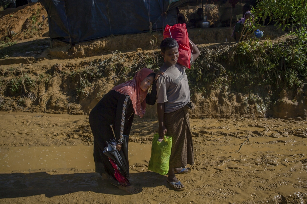 Nine months pregnant Rohingya Muslim woman, Hajira Begum. in pain leans her head on the shoulder of her husband Mohammad Sayeed as they walk toward hospital at Kutupalong refugee camp, Bangladesh, in this Sept. 24, 2017 file photo. — AP