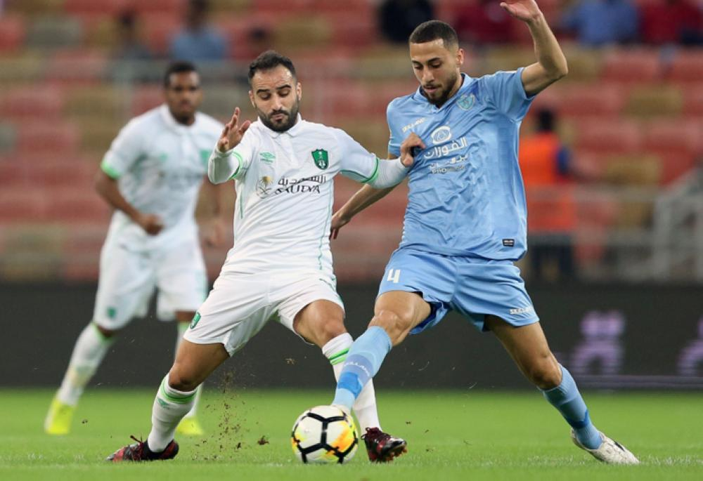 Al-Ahli's Giannis Fetfatzidis (L) vies for the ball with Al-Batin's Maan Khodari during their football match in the Saudi Pro League at the King Abdullah Sports City in Jeddah on Friday —AFP