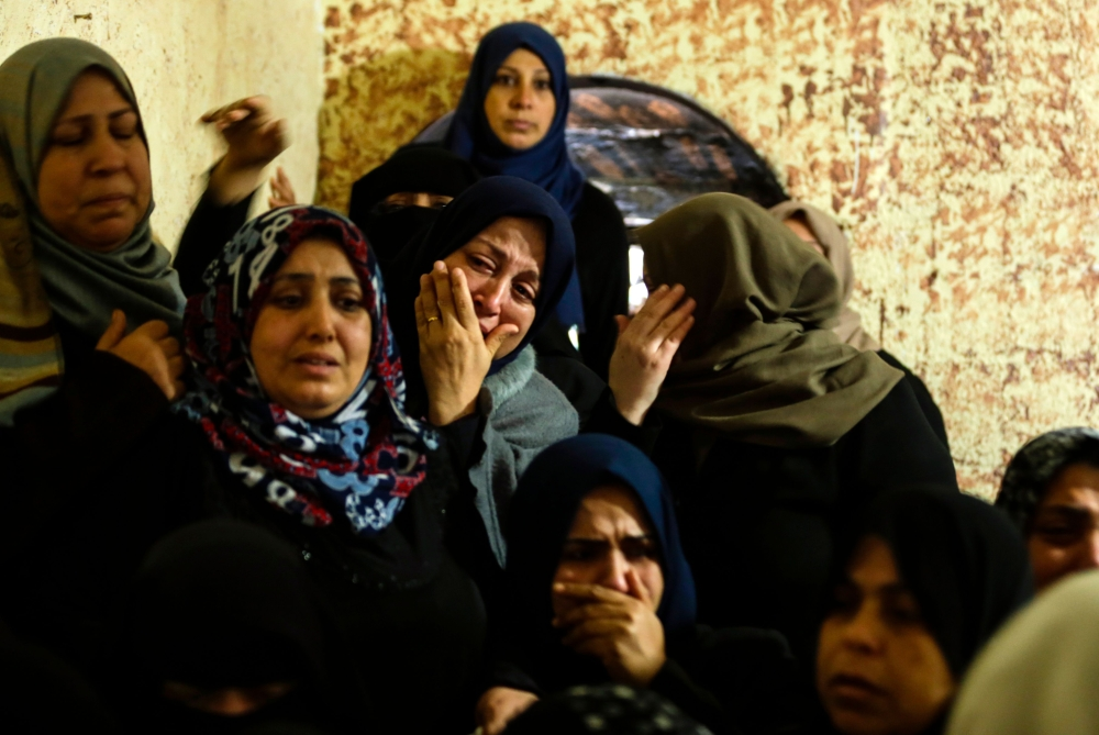 Relatives mourn during the funeral of Abdullah Zeidan, a 33-year-old fisherman, in Gaza City on Saturday. — AFP