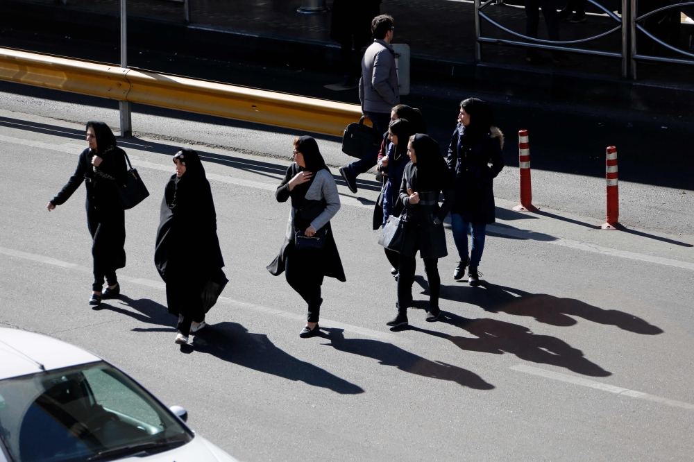 Iranian cross the road in Sadeqyeh Square in the capital Tehran. — AFP