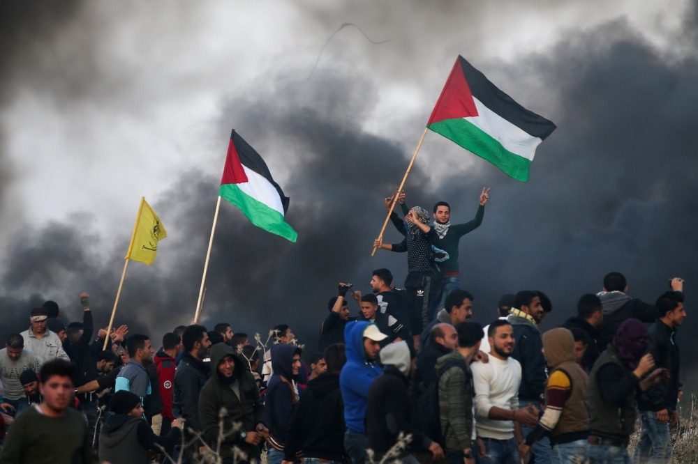 Palestinian protesters wave national flags during clashes with Israeli security forces on the eastern outskirts of Gaza City. — AFP