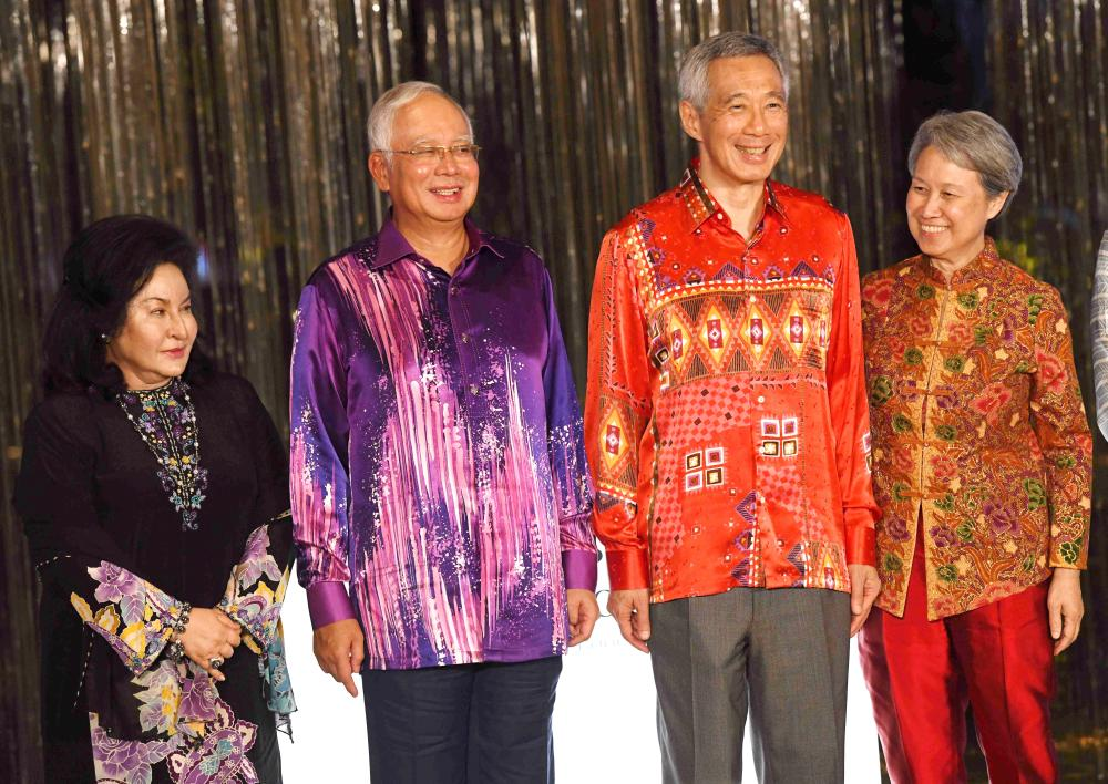 Malaysia Prime Minister Najib Razak (2nd L), his wife Rosmah Mansor (L), his Singaporean counterpart Lee Hsien Loong (2nd R)and Lee (R) attend the official opening of Marina One and DUO at the two mixed development projects developed by M S Pte Ltd, a joint venture between Temasek Holdings (Private) Limited and Khazanah Nasional Berhad in Singapore on January 15, 2018.  Najib is in Singapore to attend the 8th Singapore-Malaysia leaders retreat. / AFP / ROSLAN RAHMAN