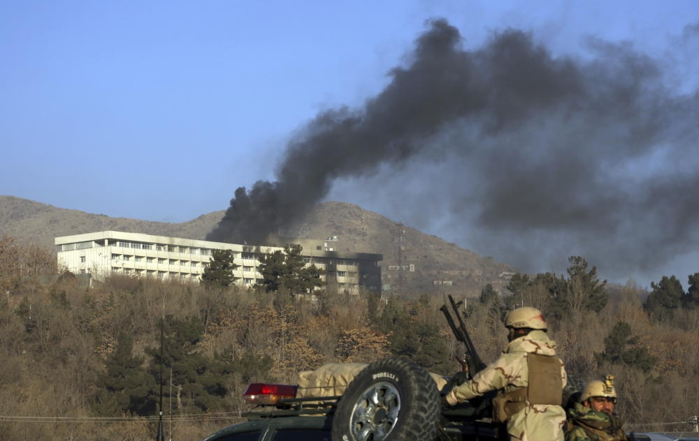 Afghan security personnel stand guard as black smoke rises from the Intercontinental Hotel after an attack in Kabul in this Jan. 21, 2018 file photo. — AP