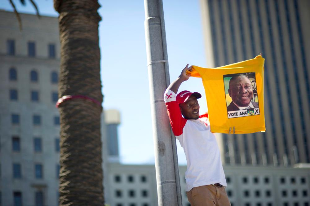 A supporter of South Africa's ruling African National Congress (ANC) holds up a shirt featuring newly-elected ANC president and South African Deputy President, Cyril Ramaphosa,  during a rally in Cape Town on Sunday. — AFP