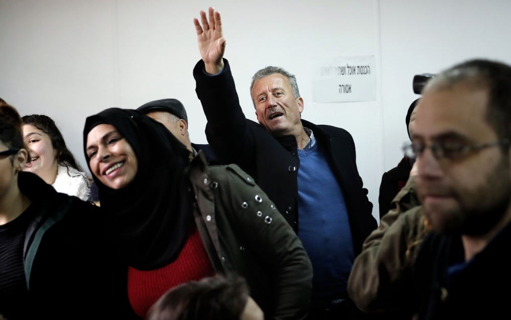 Bassem Tamimi (C), the father of 17-year-old Palestinian Ahed Tamimi waves as she arrives for the beginning of her trial in the Israeli military court at Ofer military prison in the West Bank village of Betunia on Tuesday.  — AFP