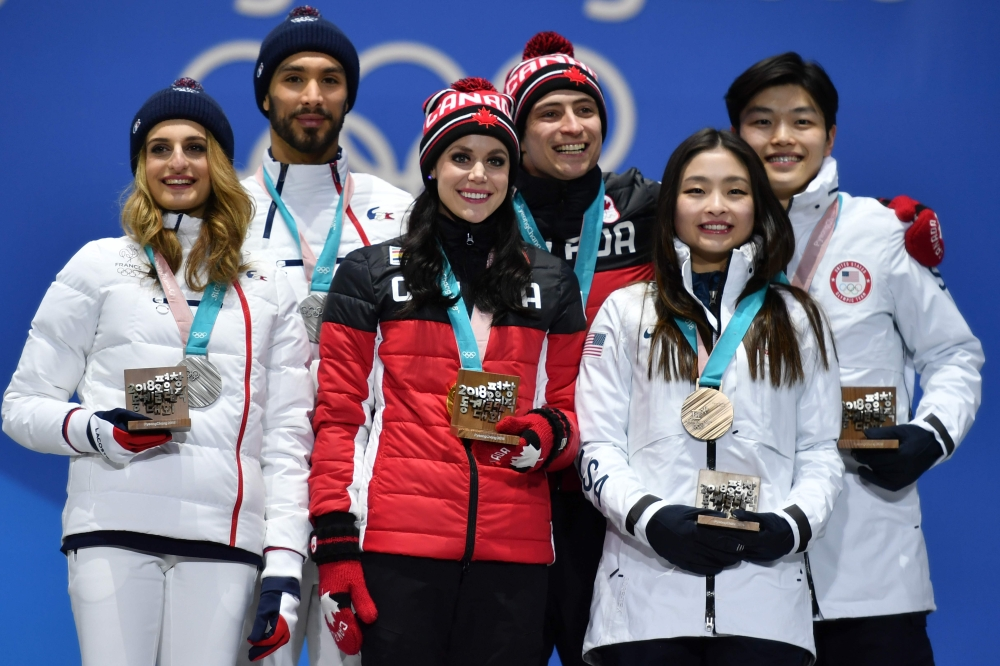 (L-R) France's silver medalists Gabriella Papadakis and Guillaume Cizeron, Canada's gold medalists Tessa Virtue and Scott Moir, and USA's bronze medalists Maia Shibutani and Alex Shibutani pose on the podium during the medal ceremony for the figure skating ice dance at the Pyeongchang Medals Plaza during the Pyeongchang 2018 Winter Olympic Games in Pyeongchang on Tuesday. — AFP