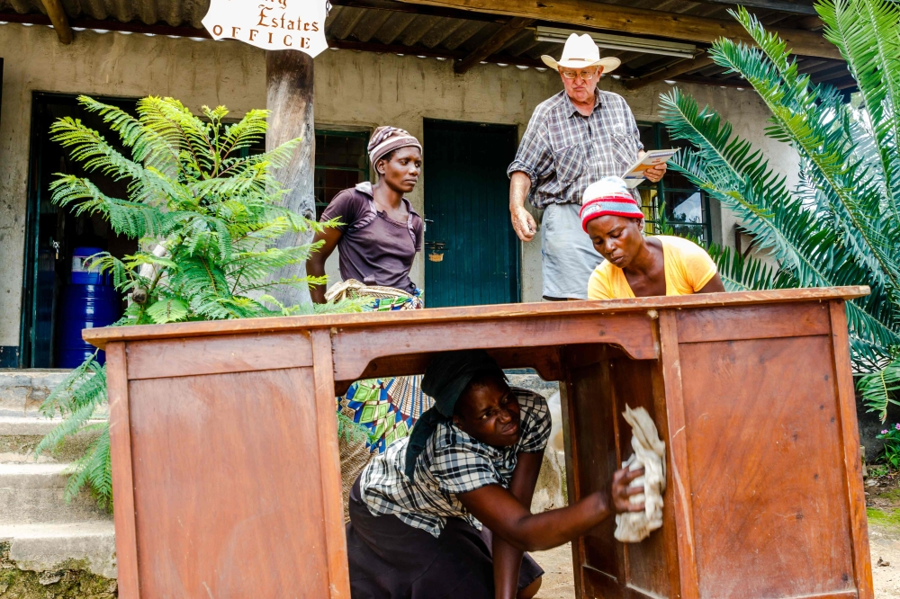 Mary Mhuriyengwe (C) leads workers cleaning an abandoned and dusty office desk for  Zimbabwean commercial farmer Rob Smart (top) at Lesbury Estates in Headlands east of the capital Harare, days after Smart was allowed to return to his land.  — AFP