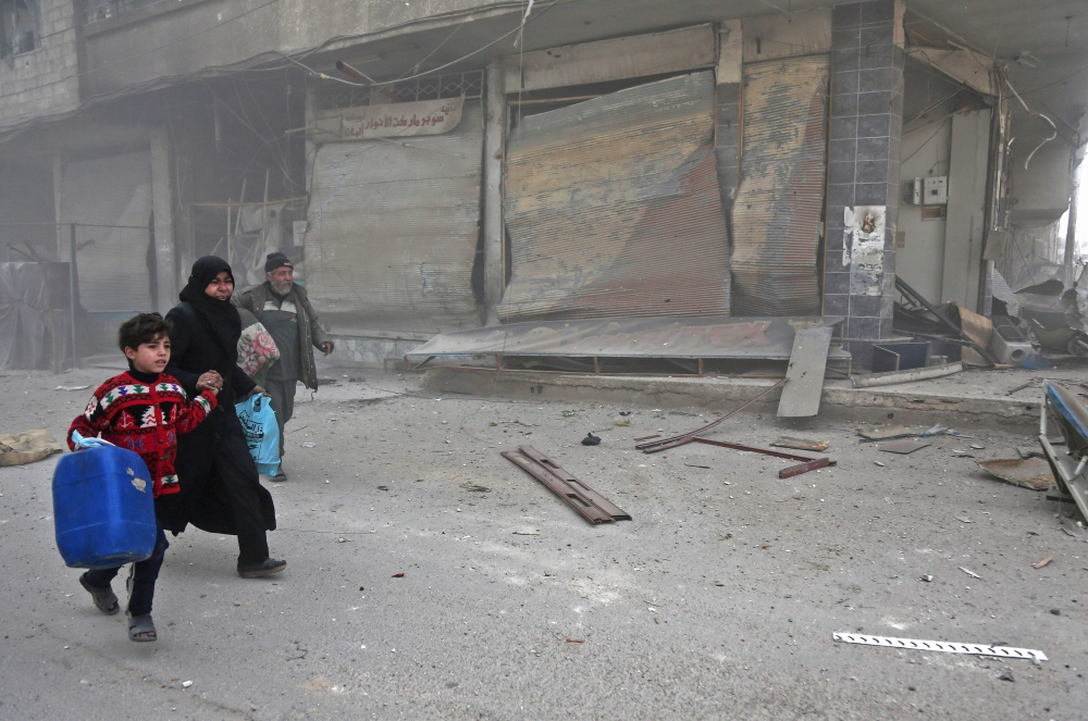 Syrians run for cover in Hamouria during shelling on rebel-held areas in the eastern Ghouta region on the outskirts of the capital Damascus. — AFP photos