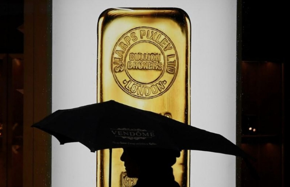 A pedestrian walks past a window displaying a representation of a gold bar at a bullion broker in Piccadilly, London, Britain, in this file photo. — Reuters