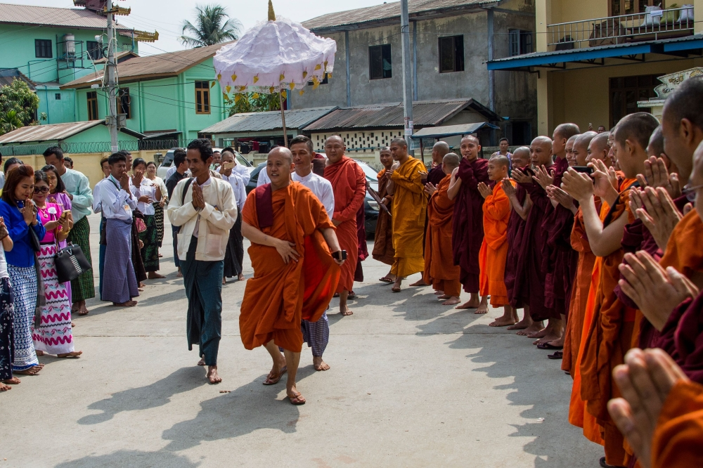 Ultra-nationalist monk Wirathu, center, arrives at a monastery in Yangon on Saturday to give a sermon marking the end of a year-long ban on public speaking. — AFP