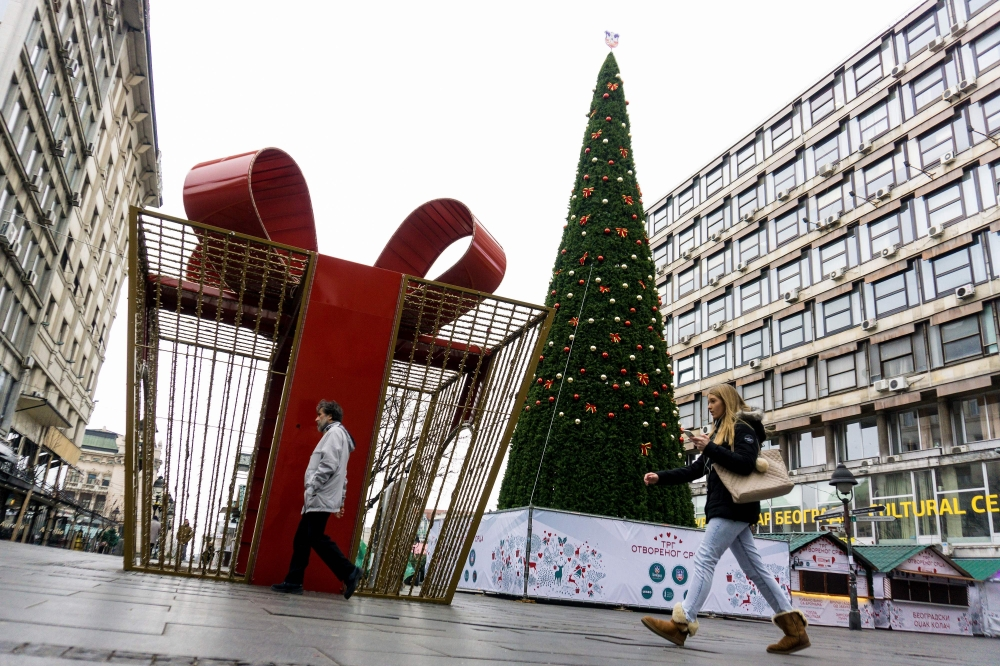 Pedestrians walk past a Christmas tree and a giant Christmas decoration in central Belgrade. Year end decorations will be dismantled only in March said Belgrade mayor Sinisa Mali. The 18-metre (59-feet) tall Christmas tree in Belgrade's pedestrian zone sparked controversy as its price, 83,000 euros, makes it one of the most expensive in the world. - AFP