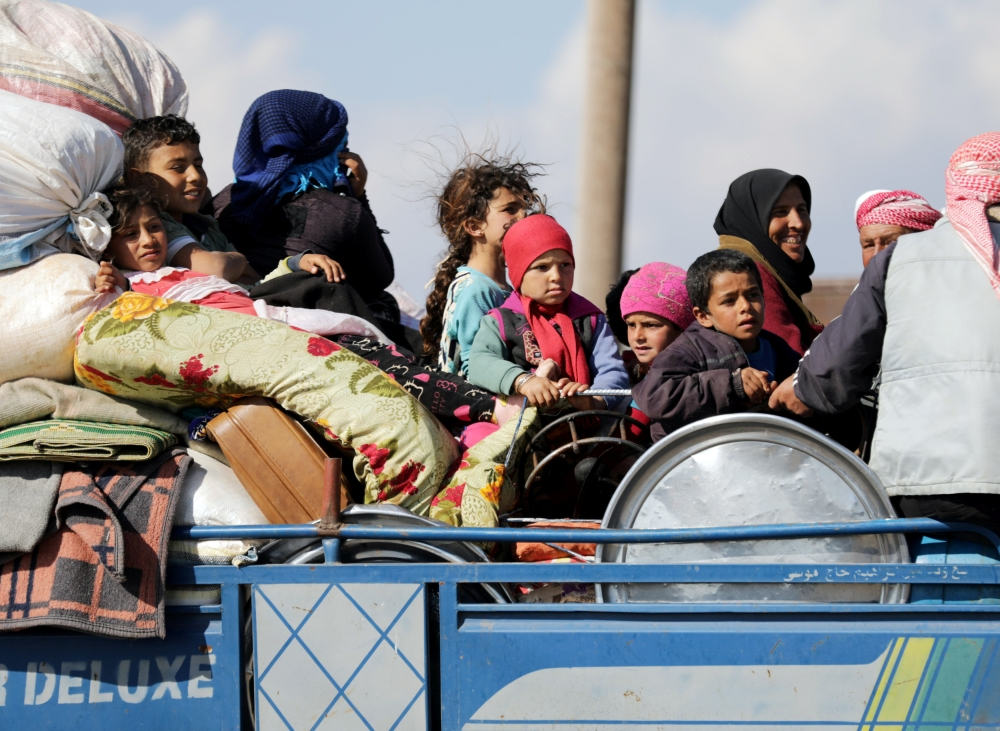 Internally displaced people ride on the back of a truck with their belongings in the town of Inab, eastern Afrin. — Reuters