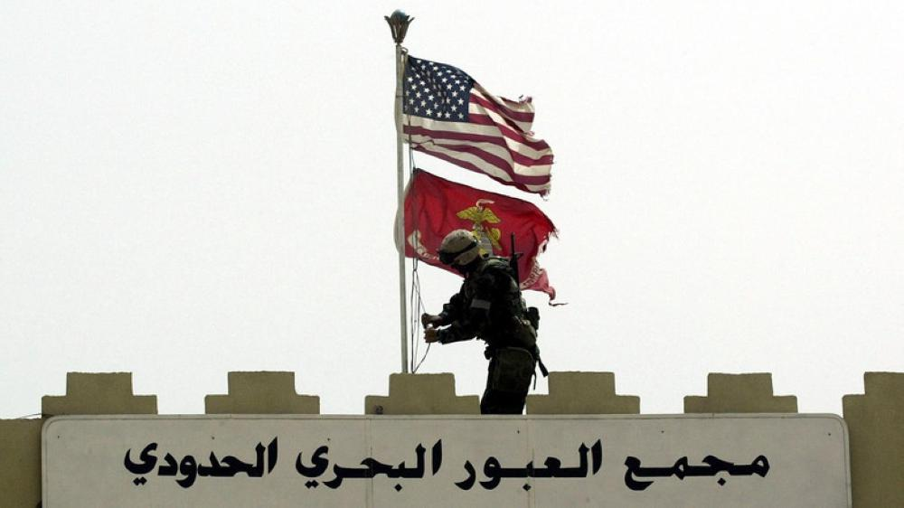 A US Marine replaces the Iraqi flag with flag of the Marine Corps, March 21, 2003. — Reuters
