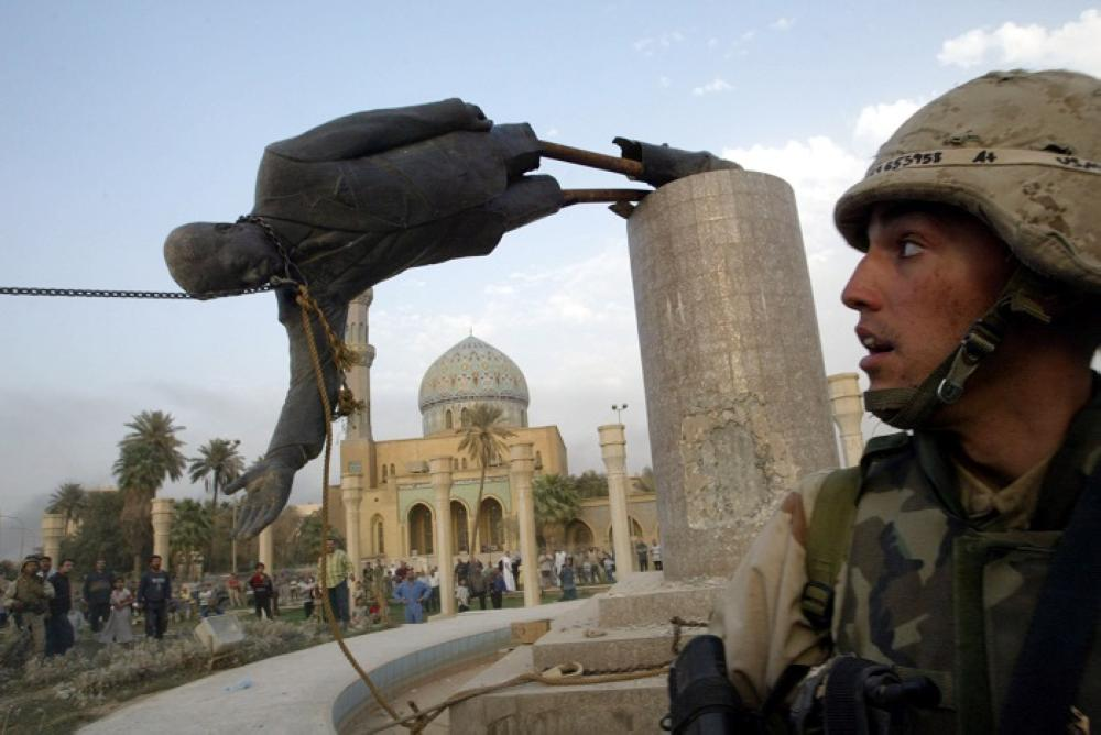 A US soldier watches as a statue of Saddam Hussein falls in central Baghdad, April 9, 2003. — Reuters