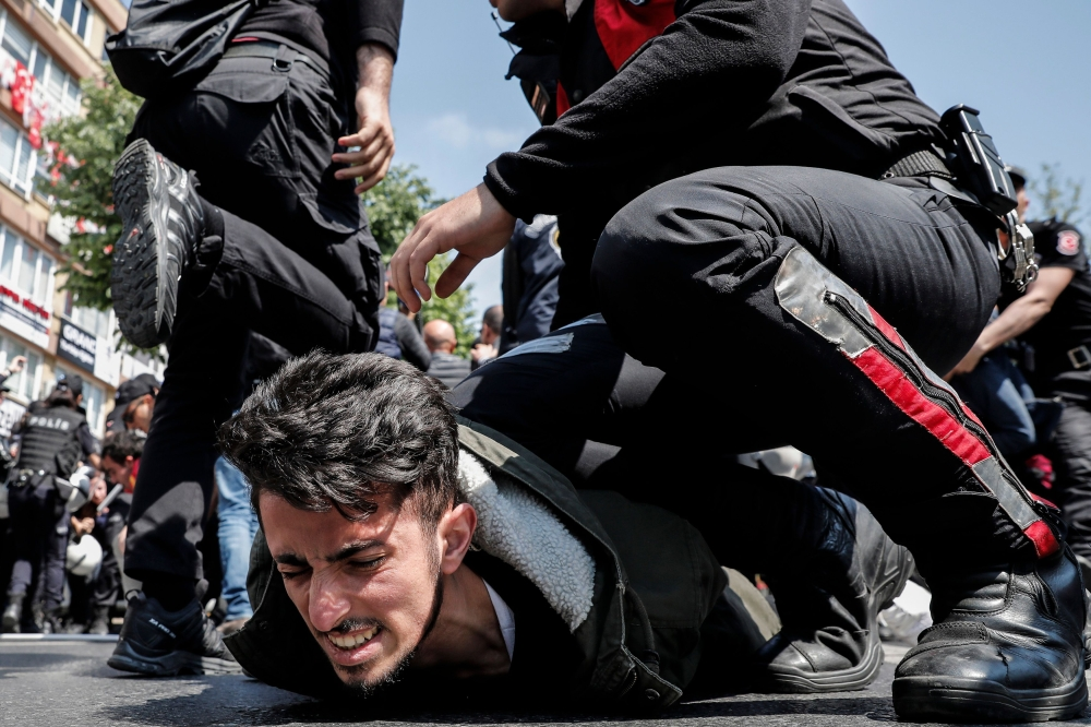 Turkish police officers arrest a protester attempting to defy a ban and march on Taksim Square to celebrate May Day in Istanbul on Tuesday. — AFP
