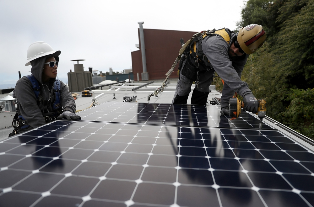 Luminalt solar installers Pam Quan (L) and Walter Morales (R) install solar panels on the roof of a home on Wednesday in San Francisco, California. The California Energy Commission passed proposed legislation that would require all new homes in the state of California to have solar panels. — AFP