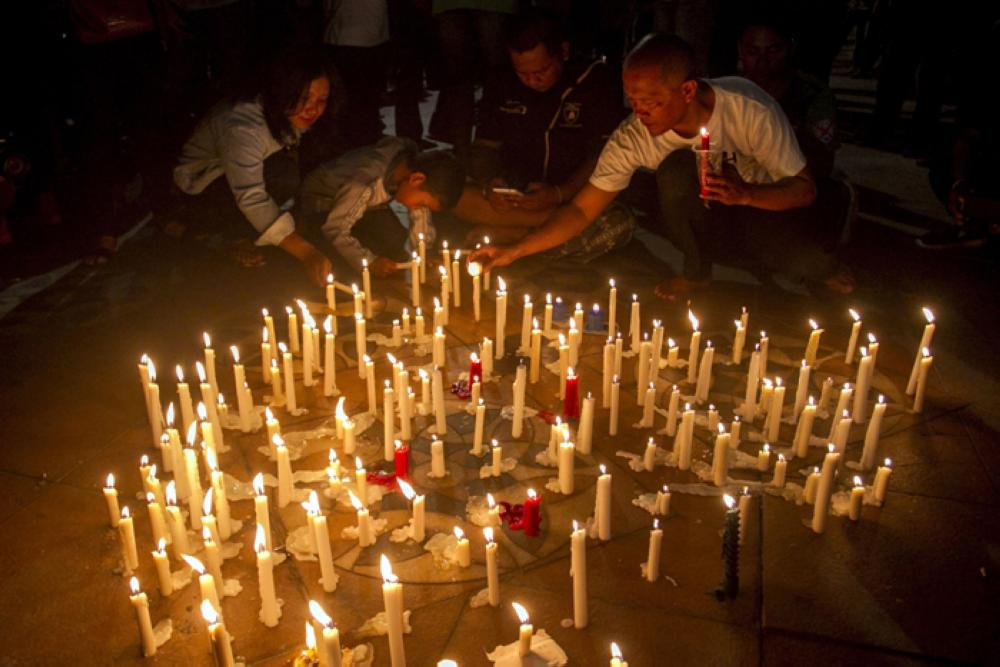 Indonesian residents light candles during a vigil for the victims of the church attacks in Surabaya, East Java, Indonesia on Sunday.