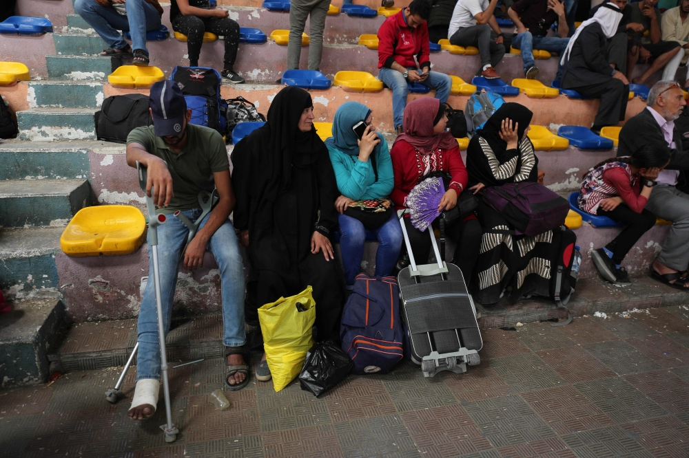 Palestinians wait to travel to Egypt through the Rafah border crossing, in the southern Gaza Strip, Friday. Egyptian President Abdel Fattah El-Sisi has made a rare decision to open the Rafah crossing with Gaza for a month, allowing Palestinians to cross during the holy period of Ramadan. — AFP