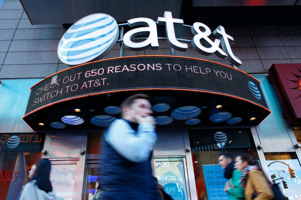 In this file photo shows people walking past an AT&T store in New York.  A federal judge will decide whether a deal between AT&T and Time Warner can go through, a deal that would transform the telecom giant into a media-entertainment powerhouse positioned for a sector facing major technology changes. — AFP