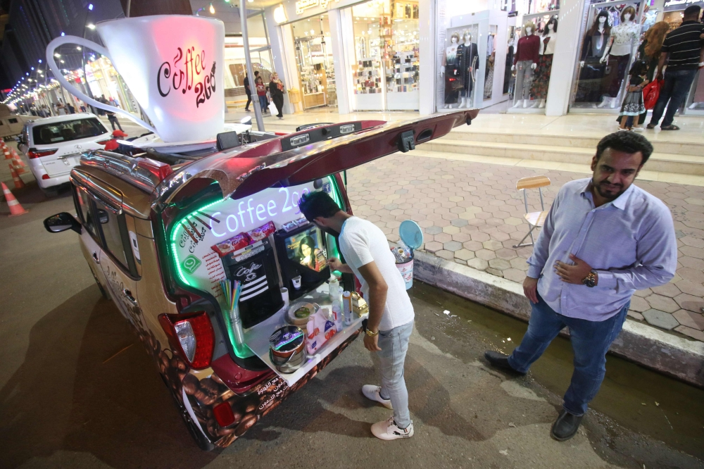 Iraqi Karrar Alaa, left, aged 26, sells coffee by his traveling cafe vehicle in a street in Basra on Sunday. — AFP