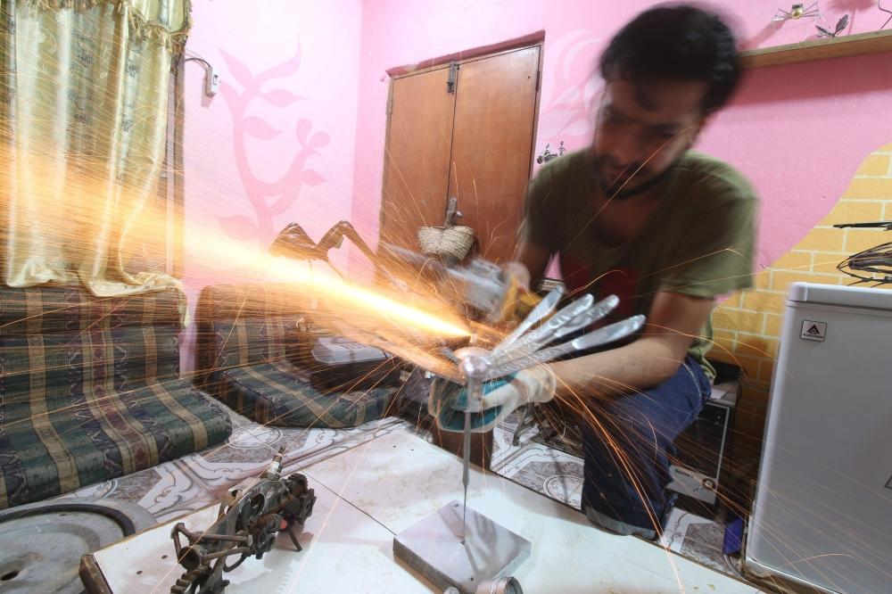 Iraqi Omar Abdallah operates at his workshop in Basra on Sunday. — AFP