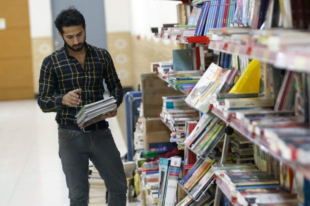 Iraqi Mashreq Jabbar, aged 26, stands at his bookstore set in a shopping mall corridor in Basra on Sunday. — AFP