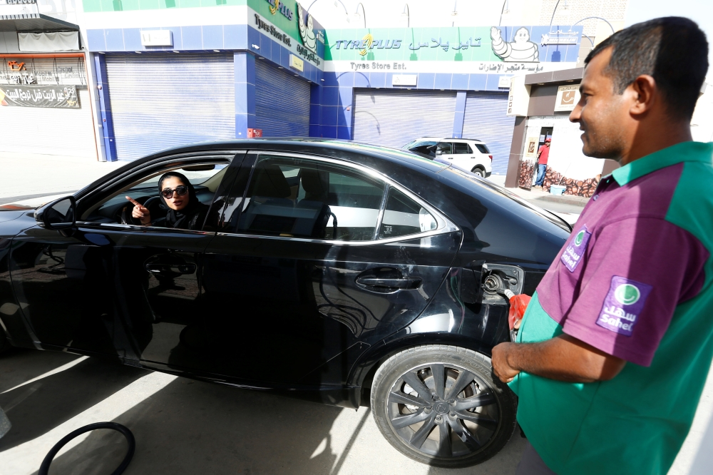 Majdooleen, who is among the first Saudi women allowed to drive in Saudi Arabia, refuels her car as she drives to work in Riyadh. — Reuters
