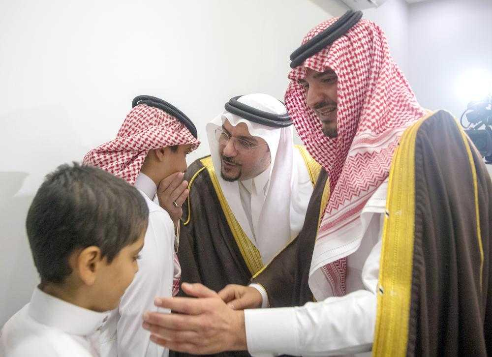 Interior Minister Prince Abdulaziz Bin Saud Bin Naif talks to the son of policeman Sulaiman Bin Abdulaziz Al-Abdullatif who was martyred in the terrorist attack on a security checkpoint in Buraidah on Sunday.