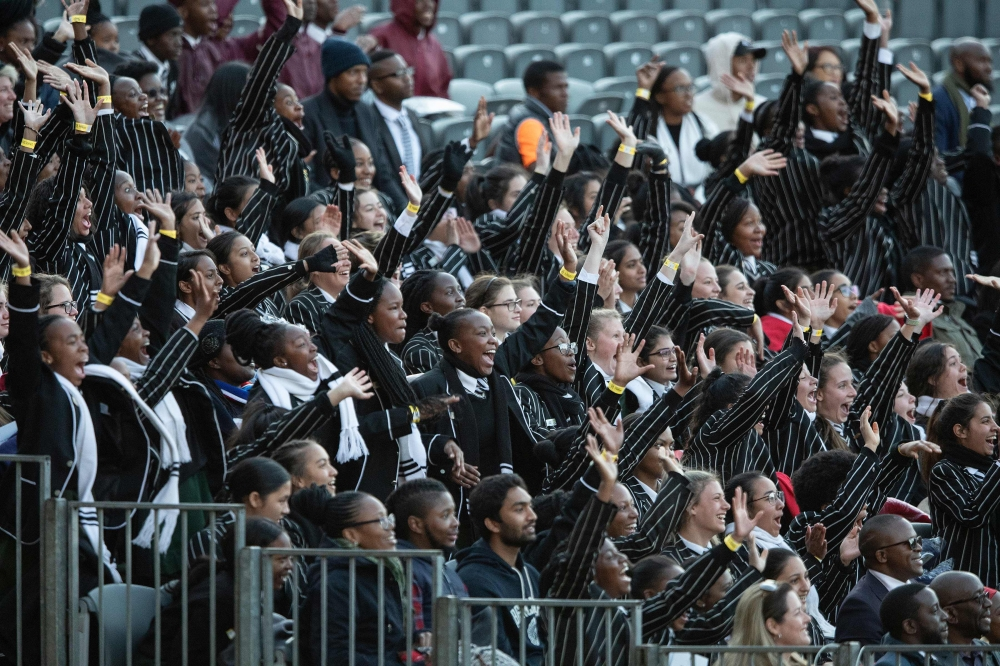 South African students raise their hands as they attend the 2018 Nelson Mandela Annual Lecture at the Wanderers cricket stadium in Johannesburg on Tuesday. — AFP