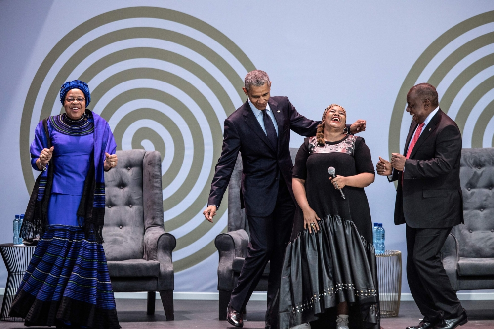 Former US President Barack Obama, second left, Graca Machel, left,  widow of former South African President and global icon Nelson Mandela, and South African President Cyril Ramaphosa, right, dance as South African singer Thandiswa Mazwai, second right, performs during the 2018 Nelson Mandela Annual Lecture at the Wanderers cricket stadium in Johannesburg on Tuesday. — AFP