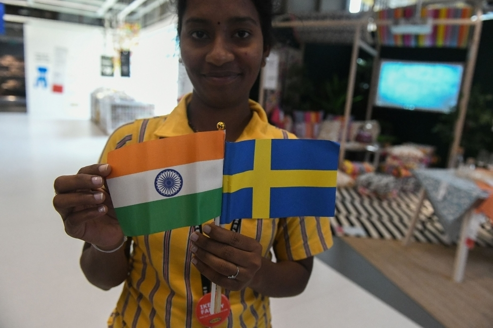An Indian worker holds flags of India and Sweden during the opening ceremony of the new IKEA store in Hyderabad on Thursday. Curious customers lay on beds and nestled into armchairs as Ikea opened its first Indian outlet, hoping to wow a burgeoning middle class with offerings tweaked to local tastes, including its famous meatballs. — AFP