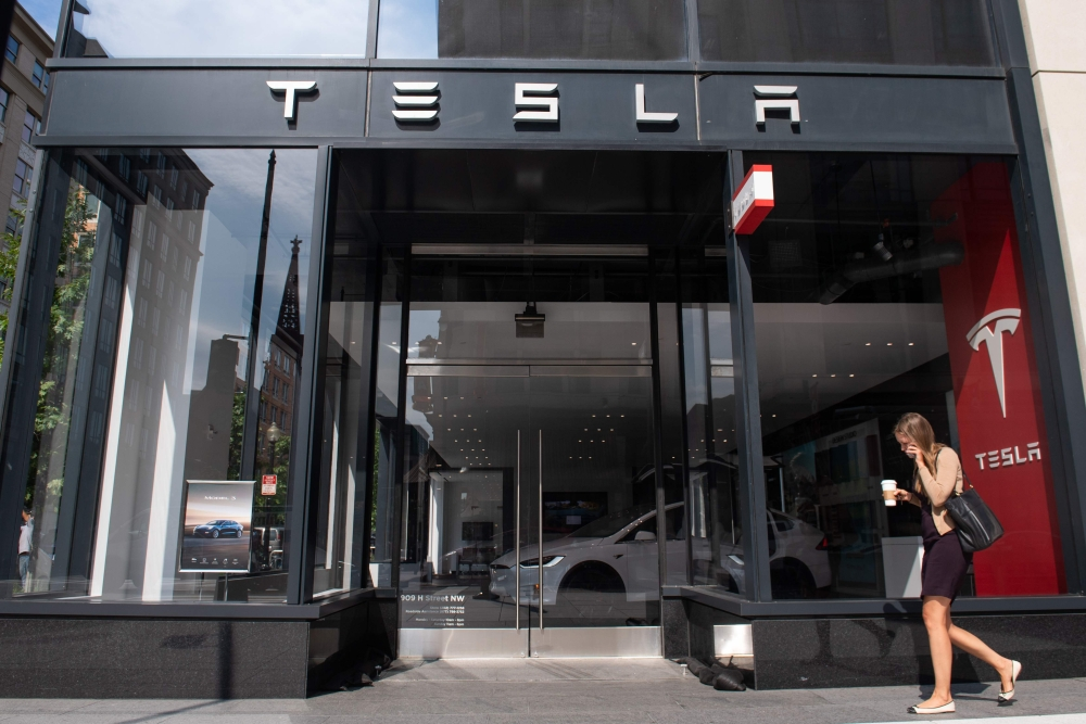 A woman walks past a Tesla showroom in Washington, DC, on Wednesday. Tesla's board of directors said Wednesday it will evaluate chief executive Elon Musk's proposal to take the electric car maker private. — AFP