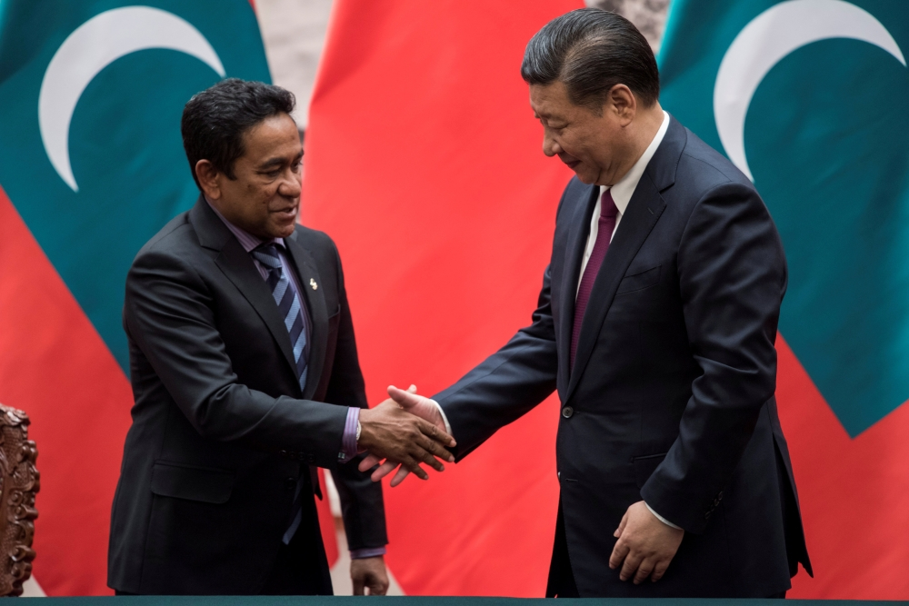 Maldives President Abdulla Yameen, left, shakes the hand of Chinese President Xi Jinping after a signing meeting at the Great Hall of the People in Beijing in this Dec. 7, 2017 file photo. — Reuters