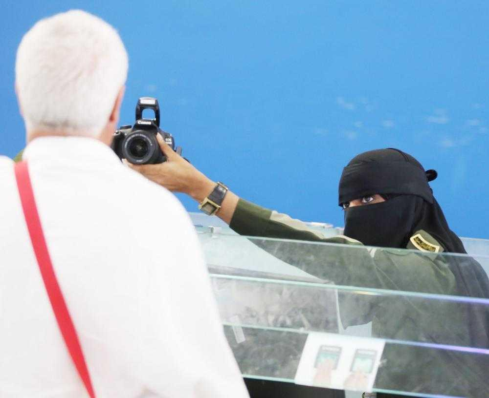 A female employee photographs an incoming pilgrim at Jeddah airport.