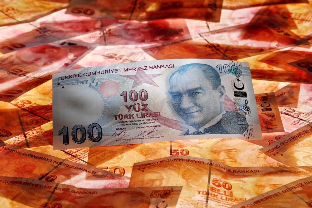 A 100 Turkish lira banknote is seen on top of 50 Turkish lira banknotes in this