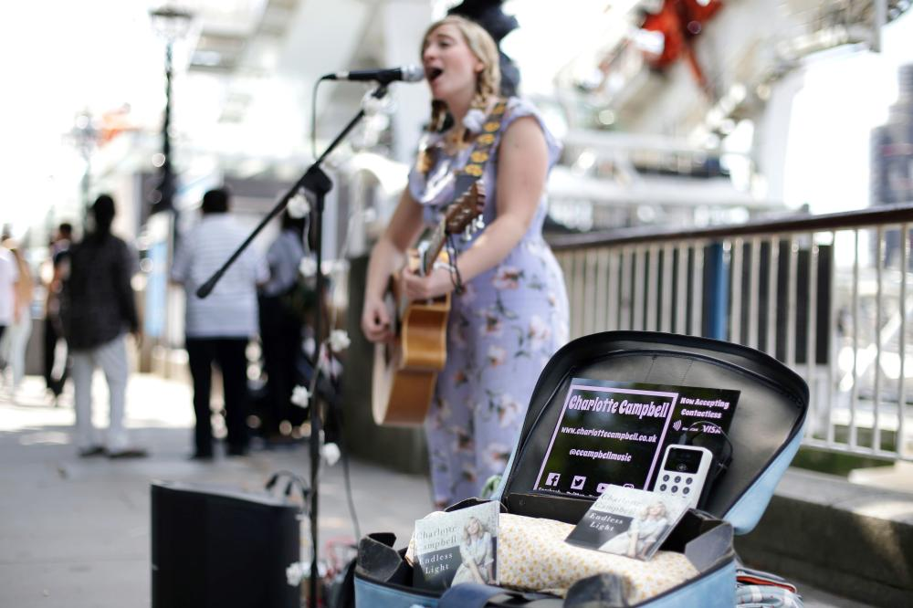 Busker Charlotte Campbell, who uses a contactless card reader for donations in addition to cash, performs near the London Eye in central London in this Sept. 1, 2018 file photo. — AFP